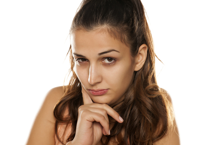 desconfianza: young woman looking at you with distrust Foto de archivo