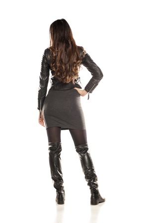 back view of pretty girl in a leather jacket and boots on white background Stock Photo