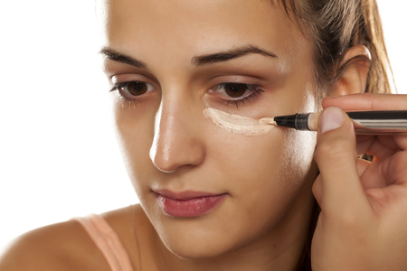 applying: young woman applied concealer on her eye circles