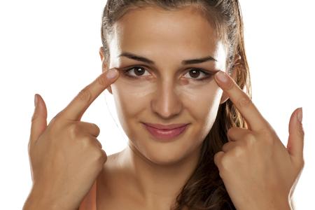 jonge vrouw toepassing concealer op haar oog kringen