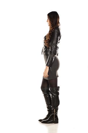 rocker girl: Vista lateral de la chica bonita en una chaqueta de cuero y botas sobre fondo blanco