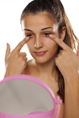 Jonge mooie vrouw heeft een beschermende room onder de ogen aangebracht Stockfoto