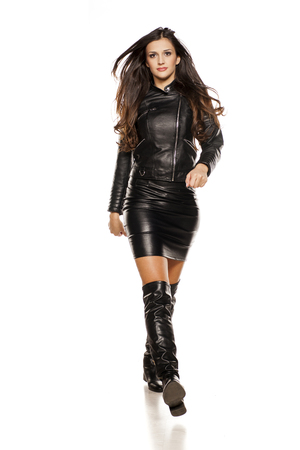 young beautiful woman walking in leather jacket, boots and skirt