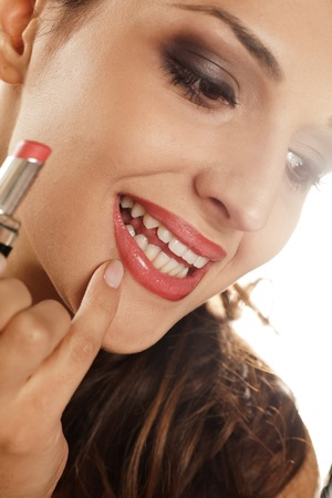 corrects: young woman corrects her lipstick with her fingers Stock Photo