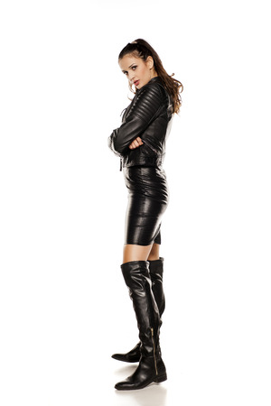 young beautiful woman in leather jacket, boots and skirt Stock Photo