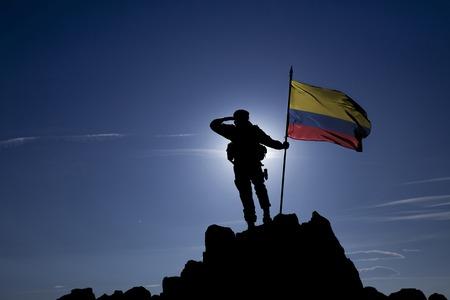 Soldado en la cima de la montaña con la bandera de Colombia Foto de archivo