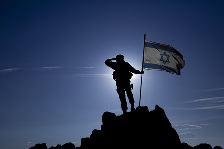 Soldier on top of the mountain with the Israeli flag Imagens