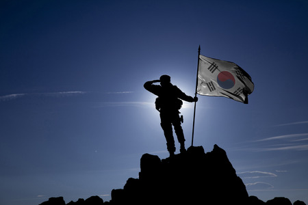 Soldier on top of the mountain with the South Korean flag