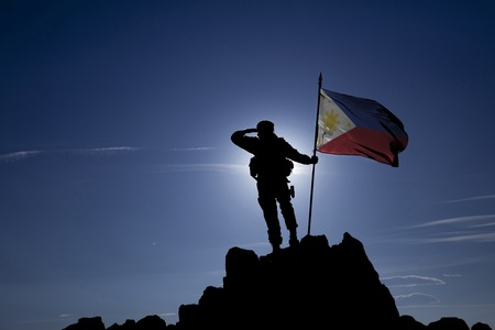 Soldier on top of the mountain with the Philippine flag