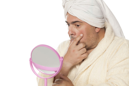 Amazed adult man with a towel on his head looking at himself in the mirror
