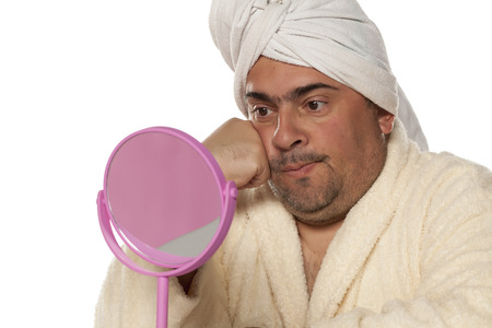 concerned adult man with a towel on his head looking at yourself in the mirror