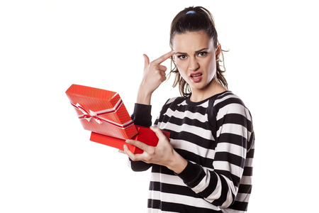 Angry girl holding a gift in her hand Stock Photo
