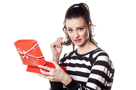 disappointed girl with questionable gesture holding a gift Stock Photo