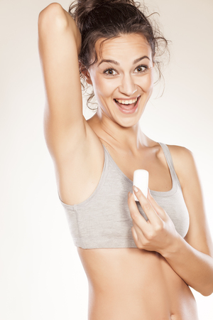 underarms: happy girl holding a deodorant stick in hand