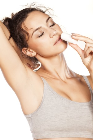 underarm: beautiful girl enjoying the scent of her deodorant stick Stock Photo