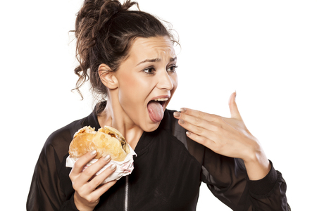 Young woman with spicy sandwich and burning tongue Stok Fotoğraf