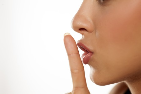 Close up finger in front of lips ... concept of silence