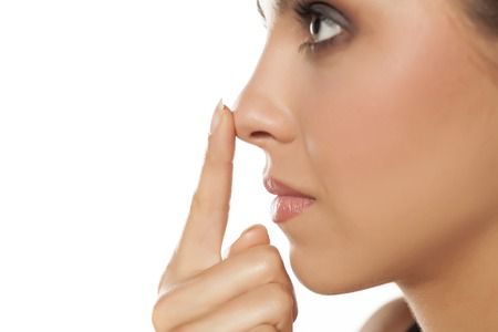 Profile of young woman touching her nose Stockfoto