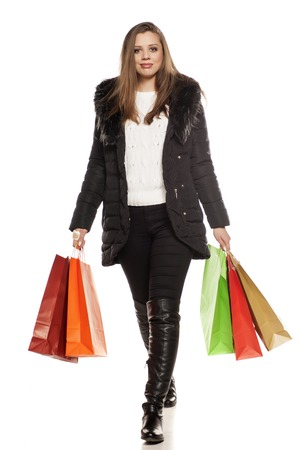 young woman in winter clothes and shopping bags walking on white background