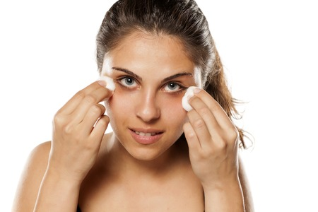young woman cleans her face using tonic and cotton pads Stock Photo
