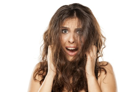 A young shocked woman with a messy long hair