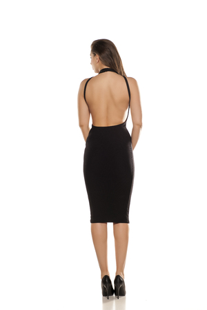 back view of young woman in tight black dress on white background