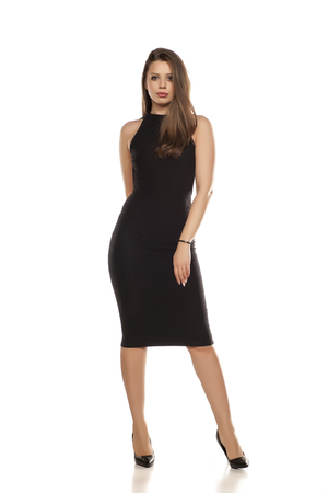 young woman in tight black dress on white background Stock Photo
