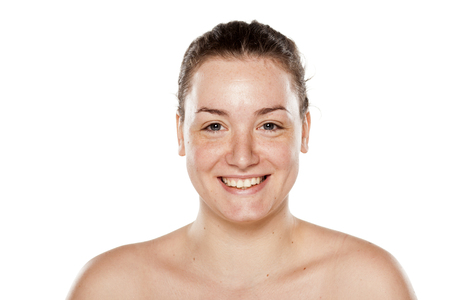 smiling young woman without makeup on white background Stock Photo