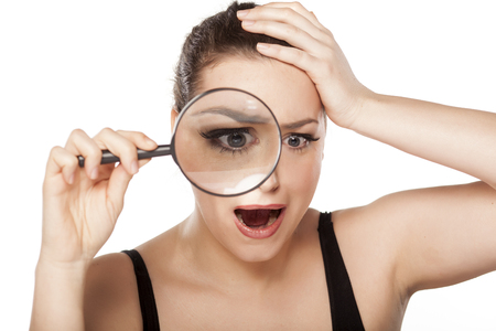 astonishing: shocked young woman looking through a magnifying glass
