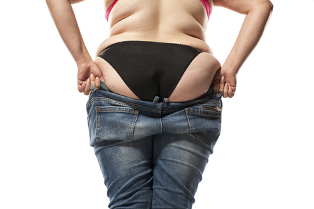 fat woman putting on tight jeans on a white background
