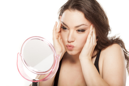aging woman: young woman in front of the mirror tightens her face Stock Photo