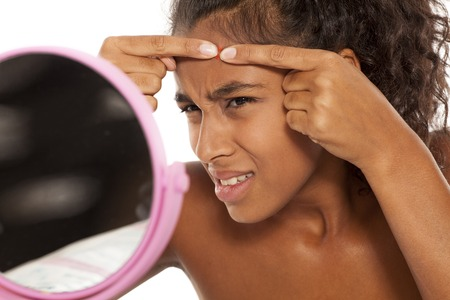 young beautiful black woman squeezing pimples on her face