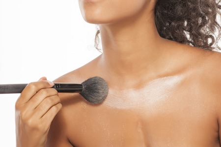 a young dark skinned woman applies a highlighter on her decolletage Stock Photo