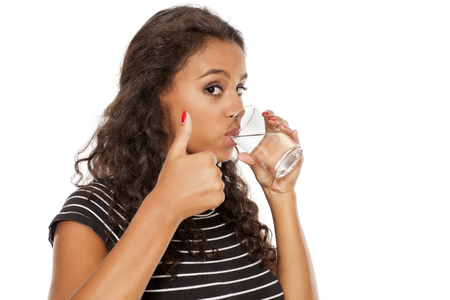 young beautiful african girl drinking water from a glass and  showing thumbs up on white background Standard-Bild