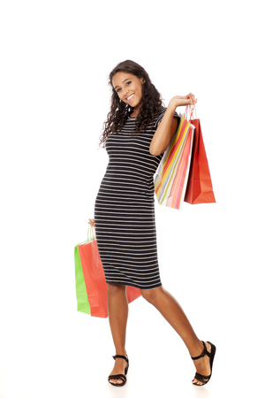 Young and happy dark skinned woman with shopping bags on white background Stock Photo