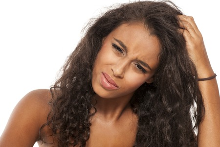 chica joven de piel oscura tiene picazón en el pelo