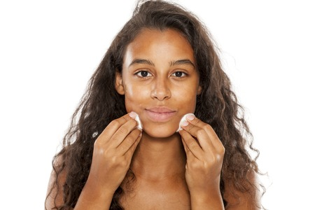 Beautiful dark skinned girl cleans her face with a cotton pad