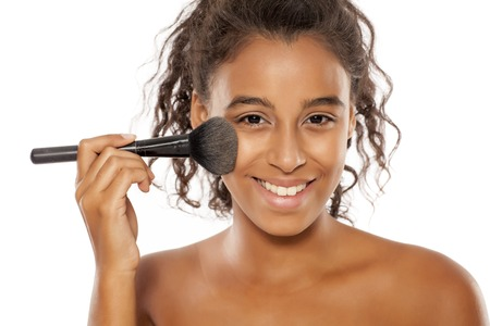 a young dark skinned woman applies a powder foundation on her face Stock Photo