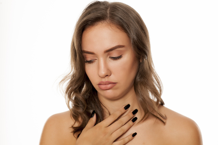 angina: Beautiful young woman has a pain in her throat on white background Foto de archivo