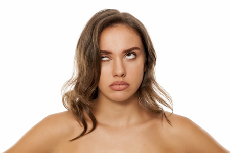 Beautiful nervous woman overturn her eyes on white background
