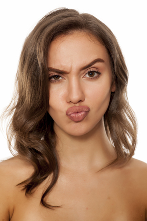 young beautiful scowling woman with pursed lips Stock Photo