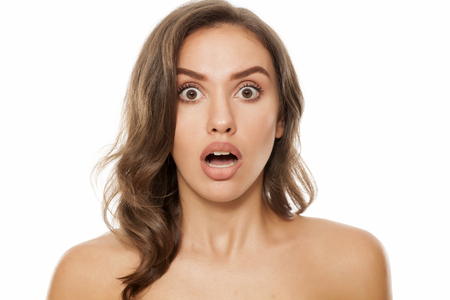 astonishing: Portrait of beautiful young shocked woman on white background