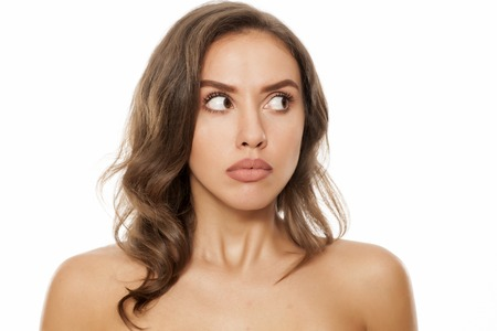 Portrait of beautiful young afraid woman on white background