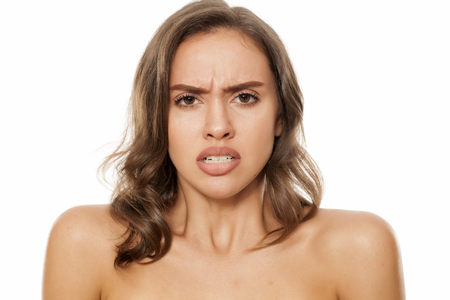 Portrait of beautiful young angry woman on white background
