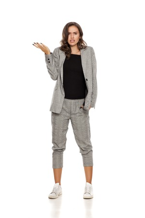 confused young beautiful woman in a jacket, blouse, sneakers and trousers