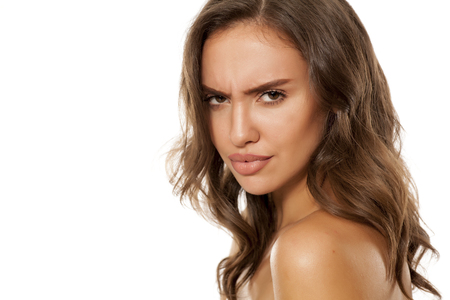 Portrait of beautiful young scowling woman on white background