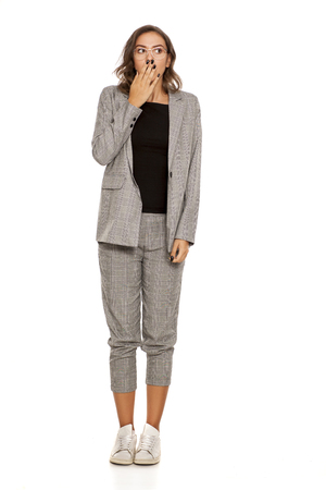 Ashamed young beautiful woman in a jacket, blouse, sneakers, trousers and glasses