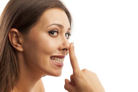 Piękna uśmiechnięta młoda kobieta dotyka jej nosa na białym tle