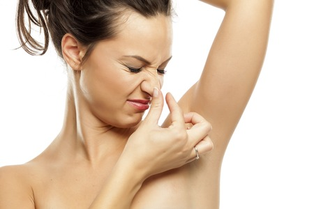 disgusted: A young woman is disgusted by the scents of her armpits Stock Photo