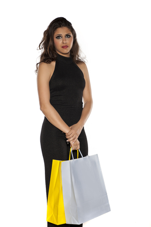 Unhappy woman in one-piece dress, trousers and blouses, holding a shopping bags